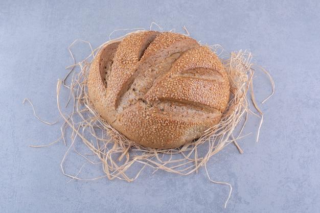 Stos słomy pod bochenkiem chleba na powierzchni marmuru