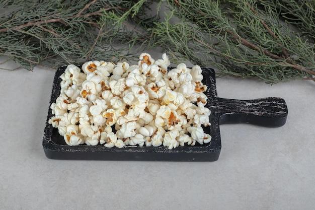 Stos słonego popcornu na drewnianej desce umieszczonej obok wiecznie zielonych gałęzi drzew na marmurowym stole.