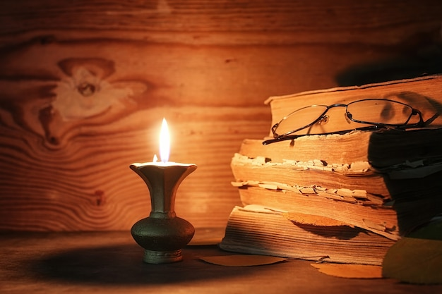 Stos starej postrzępionej książki na drewnianym stole zapalił świecę i okulary