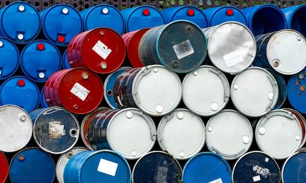 Stos starych beczek chemicznych. niebieskie, czarne i czerwone beczki po oleju.