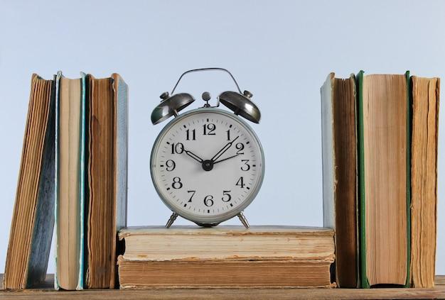 Stos starych książek i budzik na drewnianej półce przy białej ścianie