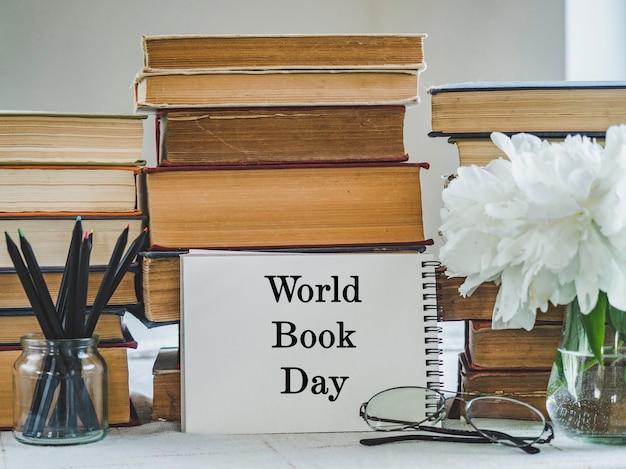 Stos starych książek i bukiet pięknych kwiatów. zbliżenie, na białym tle. zdjęcie studyjne. koncepcja uczenia się i edukacji