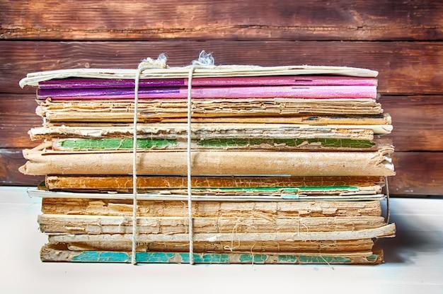 Stos starych książek i czasopism związanych sznurem na białym stole