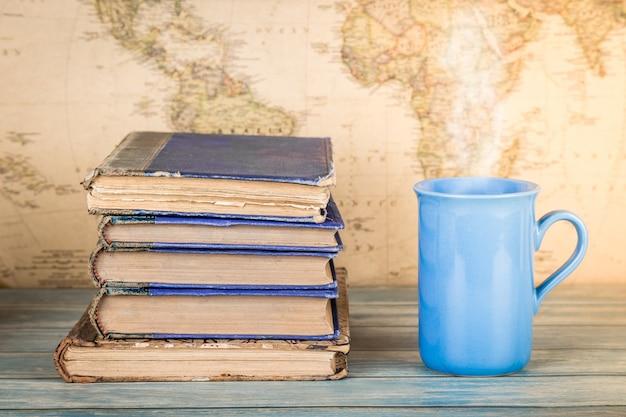 Stos starych książek i kubek gorącego napoju. tło mapy.