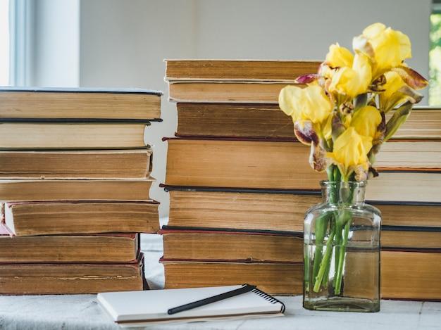 Stos starych książek i pięknych kwiatów
