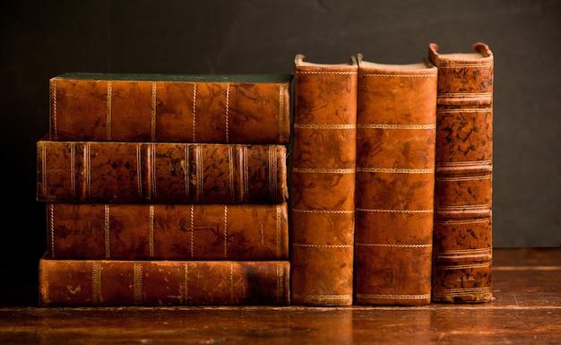 Stos starych książek na antycznej drewnianej półce i ciemnym tle
