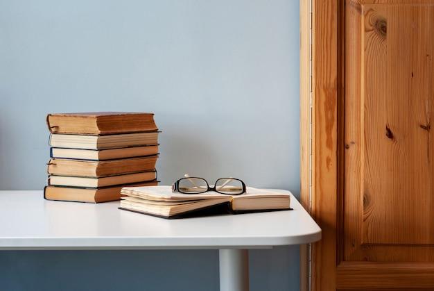 Stos starych książek na białym stole, jedna książka jest otwarta z okularami na górze.