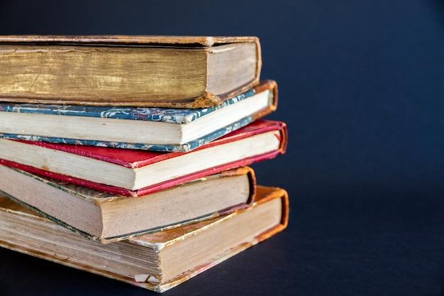 Stos starych książek na białym tle na ciemnym tle