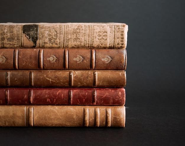 Stos starych książek na białym tle na czarnym tle