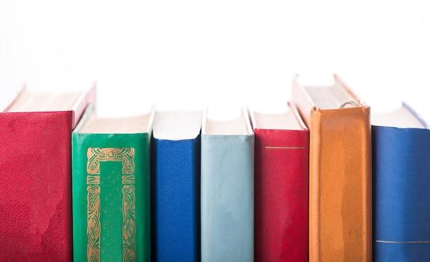 Stos starych książek na białym tle.