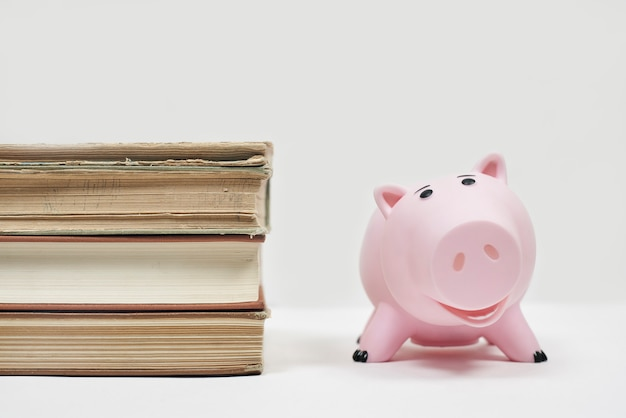 Stos starych książek z skarbonka. koszt edukacji. oszczędzanie pieniędzy na studia. oszczędzaj i płać za kształcenie dzieci w szkole wyższej