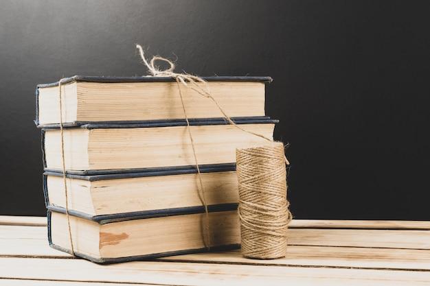 Stos starych oprawionych książek na powierzchni drewnianych z miejsca na kopię.
