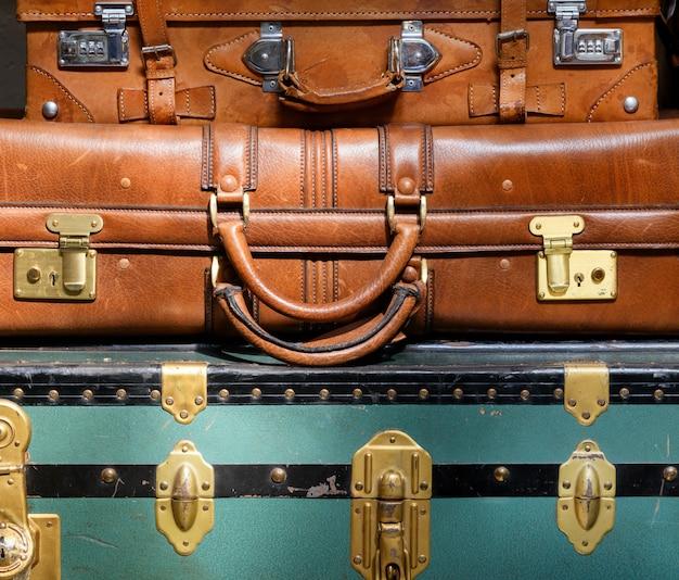 Stos starych zabytkowych bagażu z bliska z kolorowym niebieskim bagażnikiem i dwiema skórzanymi walizkami w koncepcji podróży