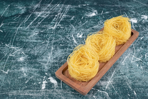 Stos surowego gniazd spaghetti na desce. wysokiej jakości zdjęcie