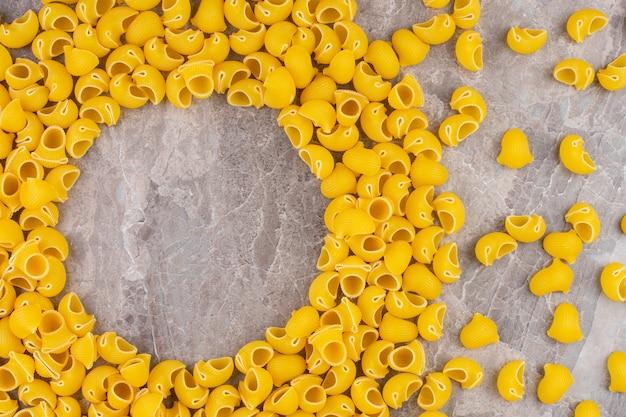 Stos surowego makaronu fajkowego na marmurze.