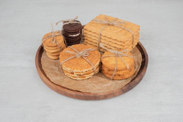 Stos świąteczne ciasteczka związane sznurem na drewnianym talerzu
