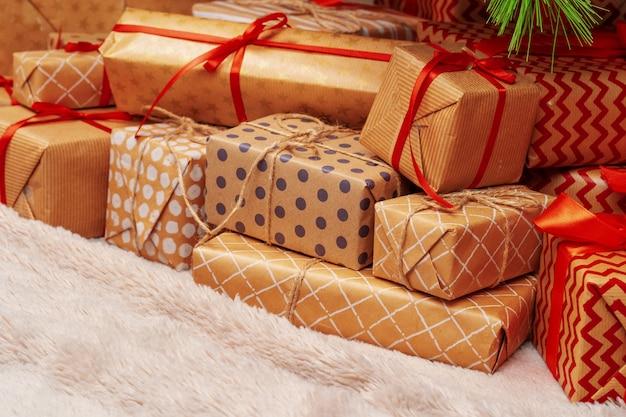 Stos świątecznych prezentów na beżowym dywanie