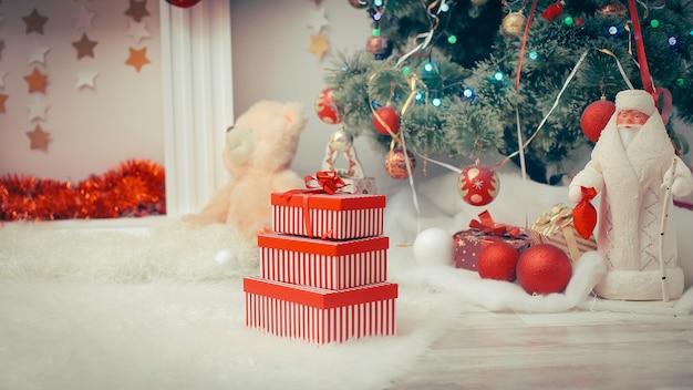 Stos świątecznych prezentów w kolorowym opakowaniu ze wstążkami pod choinką.zdjęcie z miejscem na kopię