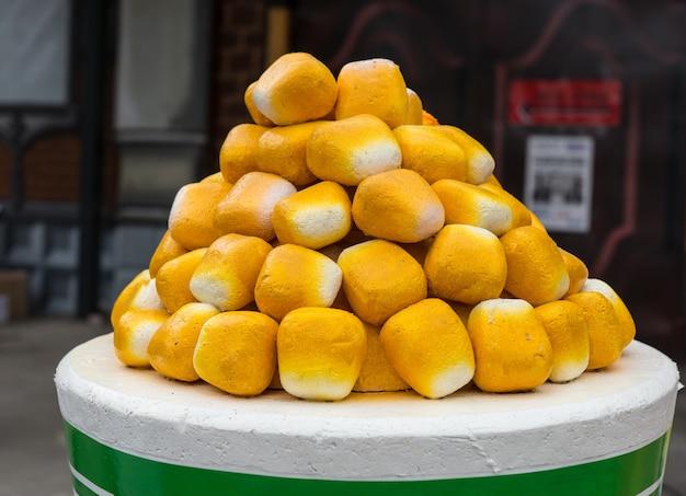Stos świeżo upieczonych bułek w formie piramidy wystawiony na okrągłym stole na imprezie gastronomicznej lub wesołym miasteczku