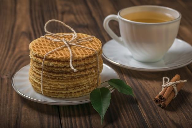 Stos świeżo zrobionych domowych gofrów i filiżanka herbaty na drewnianym stole. domowe ciasta z herbatą.