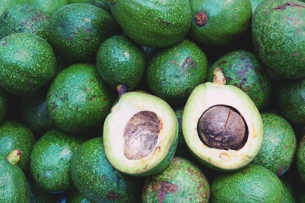 Stos świeżych awokado i pokroić pół tropikalnych owoców