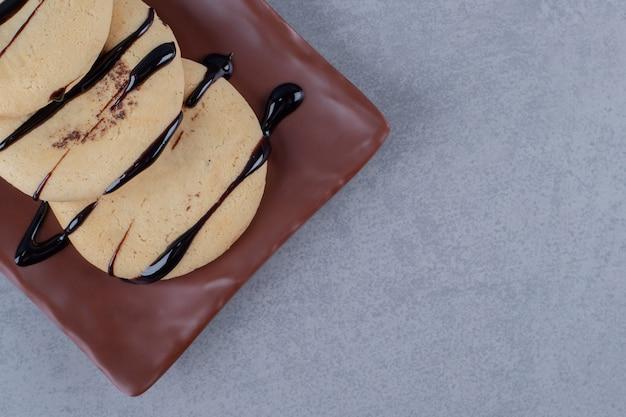 Stos świeżych ciasteczek na brązowym talerzu