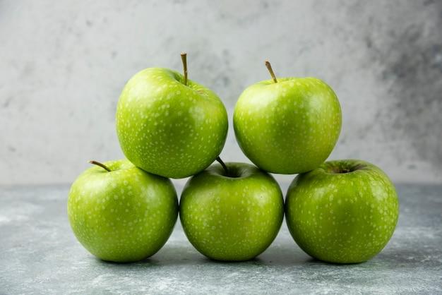 Stos świeżych jabłek na marmurze.