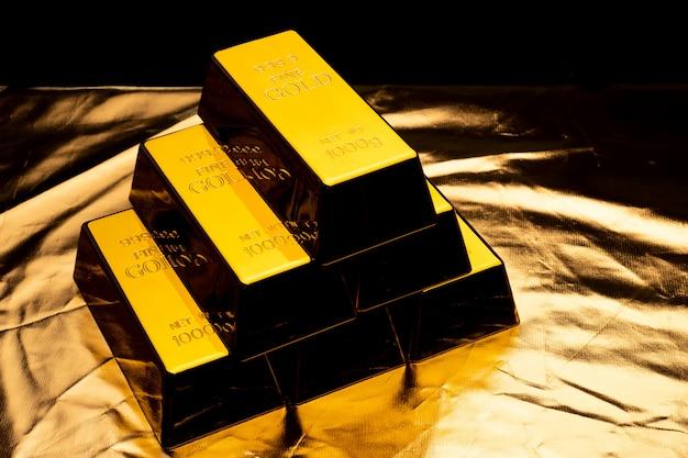 Stos sztabek złota na błyszczącym żółtym tle.