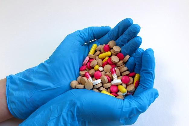 Stos tabletek w dłoniach kobiecej dłoni w rękawiczkach garść leków stosowanych w leczeniu różnych chorób