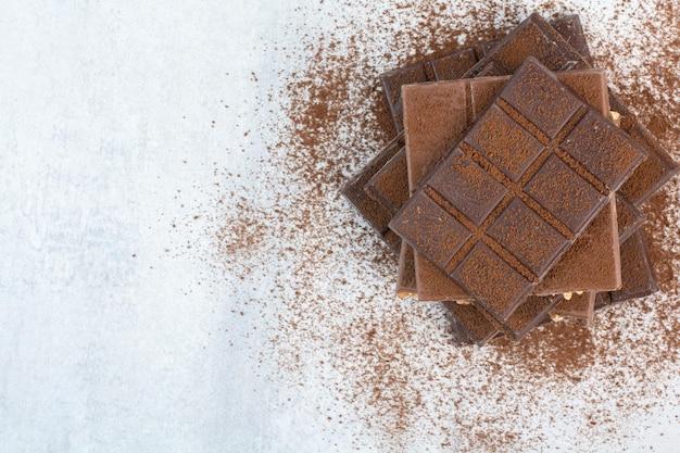 Stos tabliczek czekolady ozdobiony proszkiem kakaowym. zdjęcie wysokiej jakości