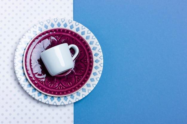 Stos talerzy ceramicznych i filiżanek do espresso. prosta konstrukcja, widok z góry z bliska. miejsce na twój tekst.