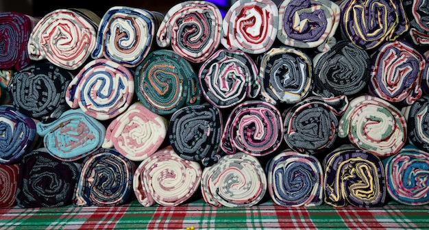 Stos tkaniny loincloth tajlandia jedwabiu. tajska rolka przepaski biodrowej na sprzedaż na targu w tajlandii