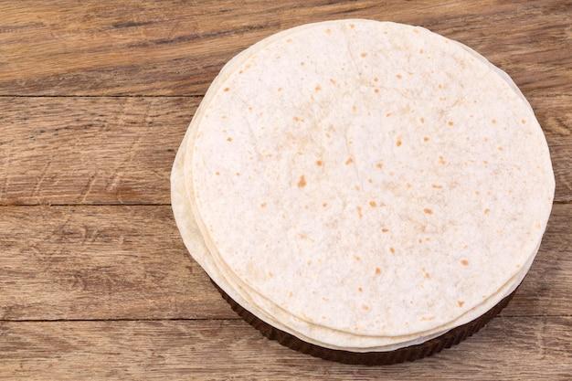 Stos tortilla domowej roboty mąka pełnoziarnista na tle drewniany stół