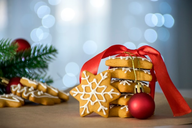Stos tradycyjnych świątecznych pierników w kształcie gwiazdy z czerwoną wstążką i zabawki z wystrojem świąt i świateł bokeh na tle