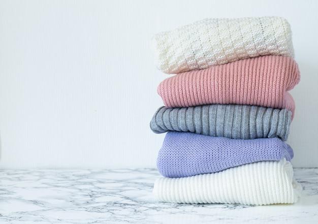 Stos ubrań w pastelowych kolorach.