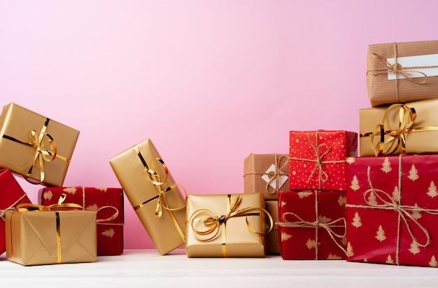 Stos ułożonych pudełek na prezent na różowym tle widok z przodu