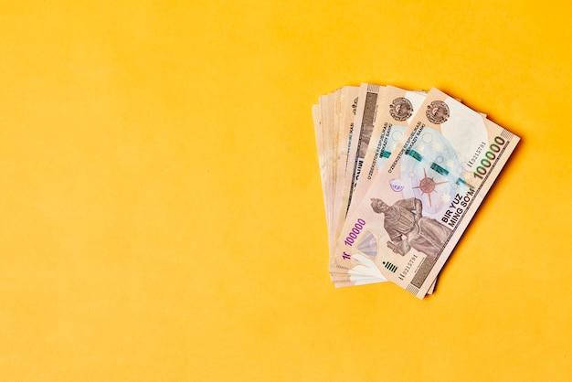 Stos uzbeckich sum uzbeckich pieniędzy na żółtym tle