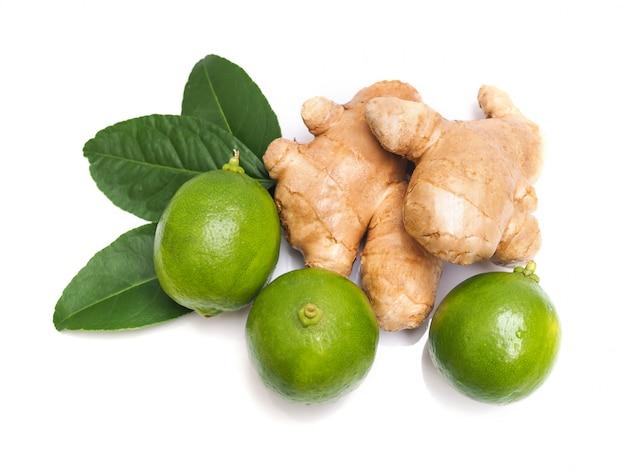 Stos wapno cytryn cytrus i świeży imbir z zielonymi liśćmi odizolowywającymi na bielu.