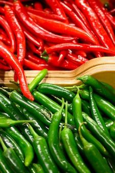 Stos warzyw czerwone i zielone papryczki chili w tle
