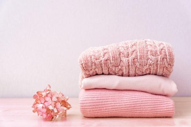 Stos wełnianych swetrów z dzianiny i kwiat