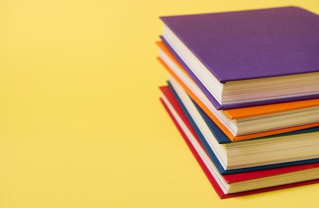 Stos wielobarwnych książek na żółtym tle powierzchni z miejsca kopiowania tekstu. koncepcja dnia nauczyciela, wiedza, literatura, czytanie, koncepcje erudycji