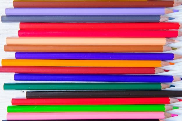 Stos wielobarwnych ołówków z bliska na białym tle
