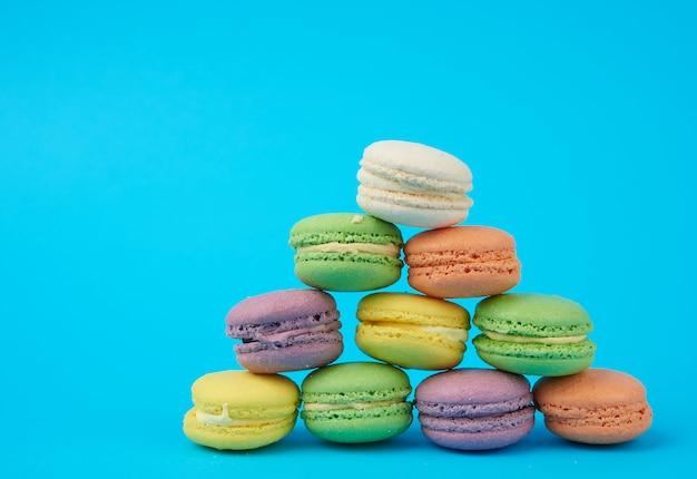 Stos wielokolorowe okrągłe pieczone ciasta macarons na niebieskim tle