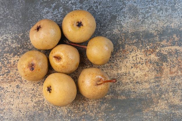 Stos zakonserwowanych jabłek na marmurze.