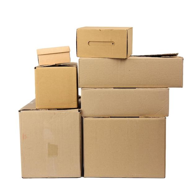Stos zamkniętych brązowych pudełkach kartonowych na białym tle