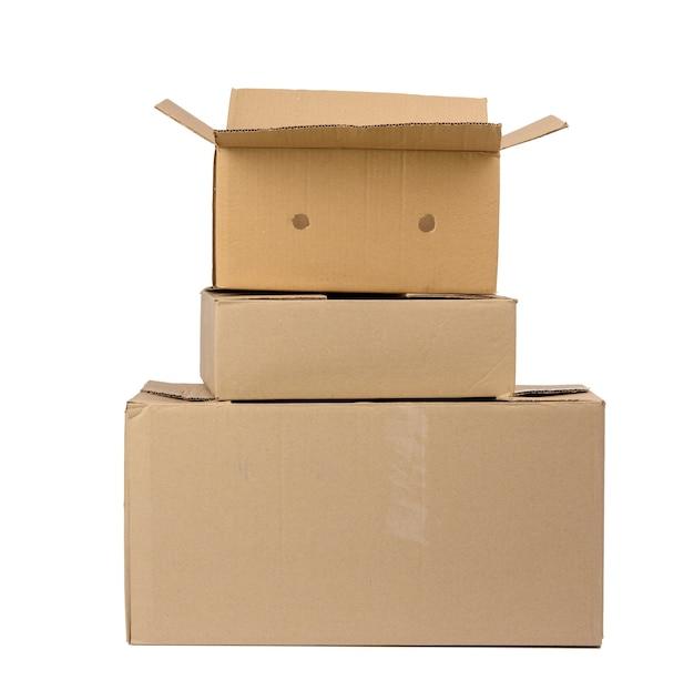 Stos zamkniętych pudełkach kartonowych brązowego papieru na białym tle, ruchoma koncepcja