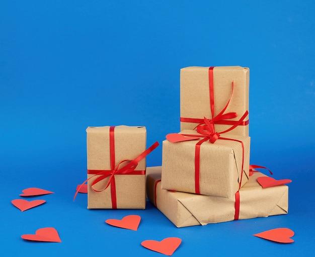 Stos zapakowanych prezentów w brązowy papier pakowy i związany czerwoną wstążką na niebiesko