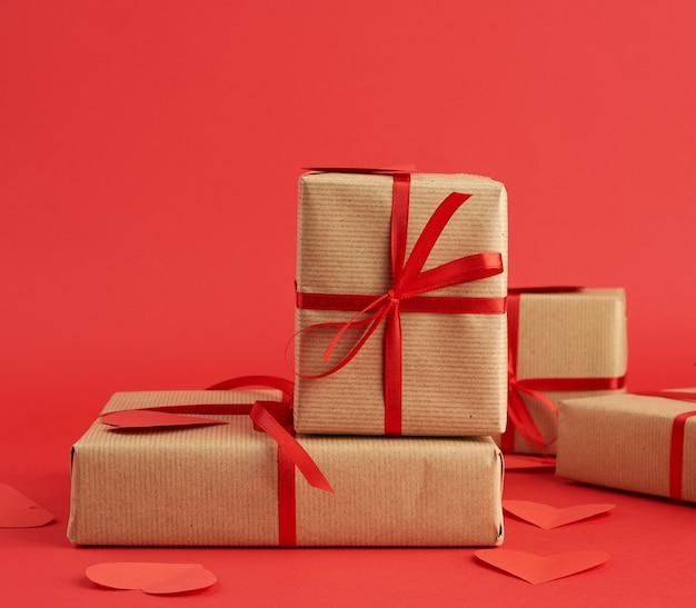Stos zapakowanych prezentów w brązowy papier rzemieślniczy i związany czerwoną wstążką na czerwono
