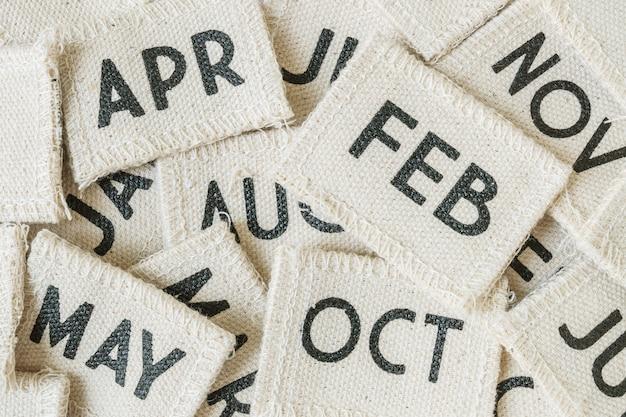 Stos zbliżenie kalendarza małych tkanin w wiele miesięcy teksturowanej tle