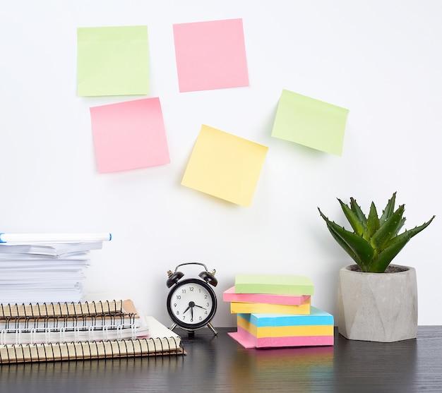 Stos zeszytów i kolorowych naklejek obok ceramicznej doniczki z kwiatkiem na czarnym stole